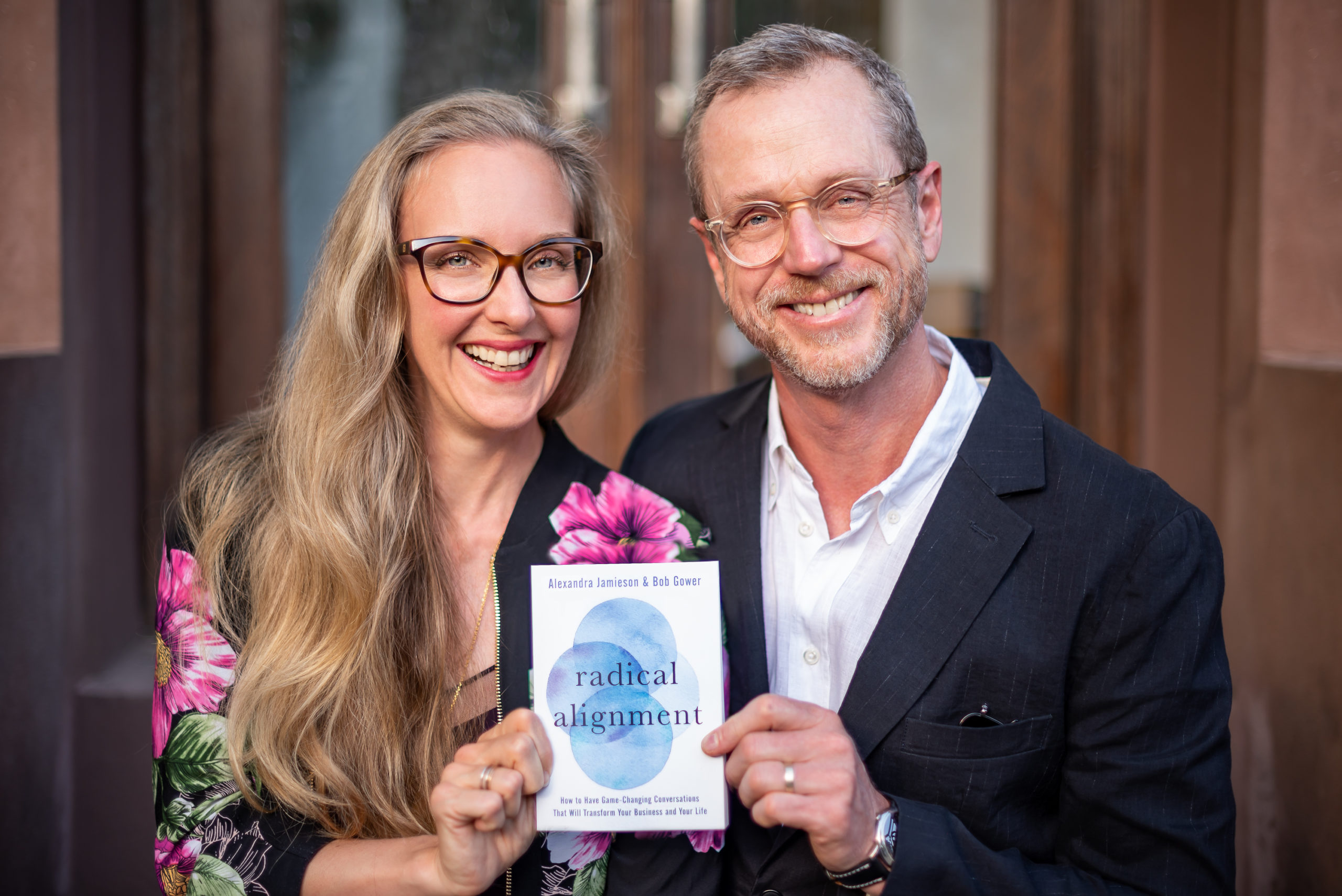 Alexandra Jamieson and Bob Gower hold a copy of their new book, Radical Alignment